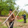 Old farmer with a wooden ladder — Stock Photo