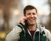 Young man speaking on phone outdoor — Stock Photo