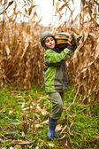 Cute little boy carrying a big pumpkin — Stock Photo
