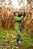 Cute little boy carrying a big pumpkin — Stock Photo