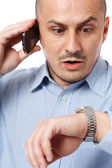 Late businessman looking at watch — Stock Photo
