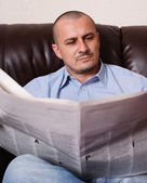 Young man with newspaper — Stock Photo