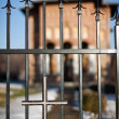 Selective focus on cross on the fence, church in background — Stock Photo #4599015