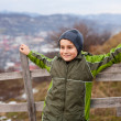 Kid sitting on wooden fence — Stock Photo