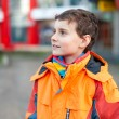 Boy in orange coat in urban environment — Stock Photo #4599107