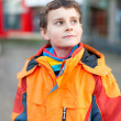 Stock Photo: Boy in orange coat in urbenvironment