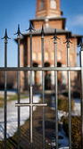 Selective focus on cross on the fence, church in background — Stock Photo