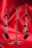 Handmade earrings over red background — Stock Photo