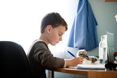 Schoolboy doing homework at his desk — Stock Photo