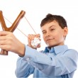 Boy sending messages on crumpled paper with slingshot — Stock Photo #4817389