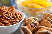 Cookies and pretzels in bowls, shallow DOF — Stock Photo