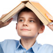 Schoolboy with a book on his head — Stock Photo #5009652