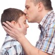 Father kissing his son on the forehead - Stock Photo