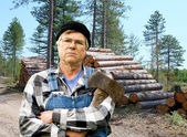Lumberjack portrait against a stack of logs — Stock Photo
