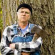 Man holding an axe leaning against a tree — Stock Photo