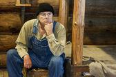 Mann sitzt in seinem blockhaus-denken — Stockfoto
