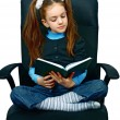 Girl reading a book in chair — Stockfoto