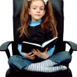 Girl reading a book in chair — Stock Photo
