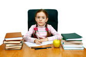 Girl being at a writing table with books — Stock Photo