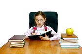 Girl which reads a book at the writing table — Stock Photo