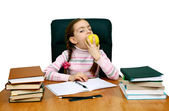 Girl with an apple being at a writing table with books — Stock Photo