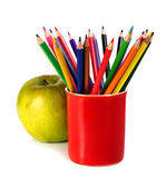 Coloured pencils and green apple — Stock Photo