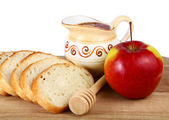 Honey in a jug and loaf apple on board — Stock Photo