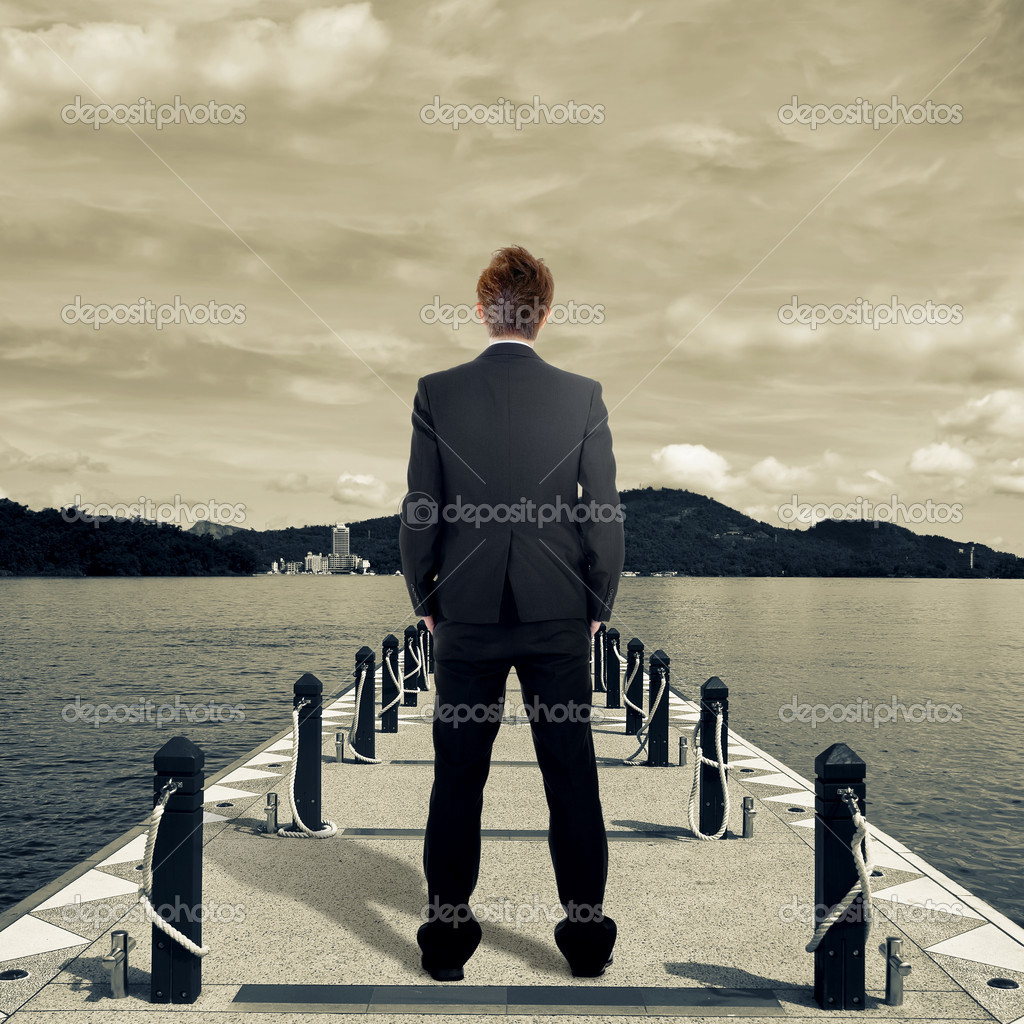 Business man standing on dock near lake. — Stock Photo #5019194