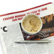 Coffee cap with french newspaper — Stock Photo