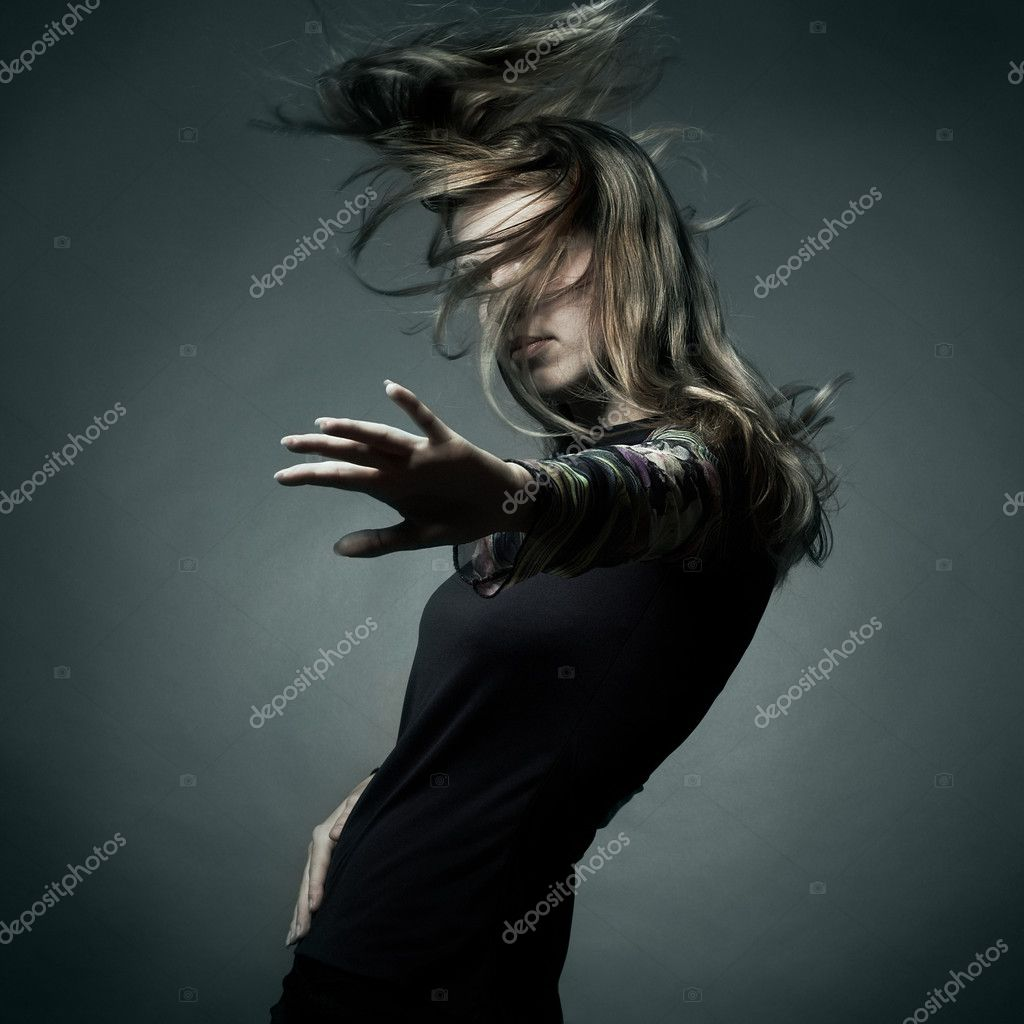 Fashion portrait of the beautiful woman with flying hair in studio  Stock Photo #4053914