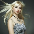 Fashion portrait of the young blonde woman with flying hair — Stock Photo #4334289