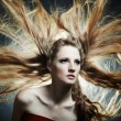 Fashion portrait of the young sexy woman with flying hair — Stock Photo