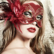 beautiful young woman in a red mysterious venetian mask on a gold backgroun — Stock Photo
