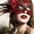 Beautiful young womin red mysterious venetimask on gold backgroun — Stock Photo #5152921