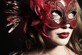 Beautiful young woman in a red mysterious mask — Stock Photo