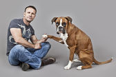 Handsome muscle man with his dog — Stock Photo