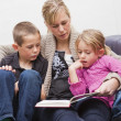Mother reading a book to her children — Stockfoto