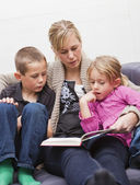 Mother reading a book to her children — Stock Photo
