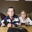Siblings playing video games — Stockfoto