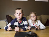 Siblings playing video games — Stock Photo