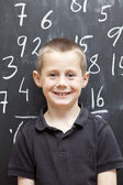 Young Boy in front of the blackboard — Stock Photo