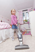 Young Girl with a vacuum cleaner — Stock Photo