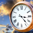 Copper clock on sunset sky — Stock Photo