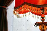 Orange lamp against drapes — Stock Photo