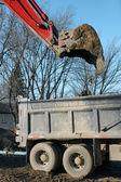 Red digger dumping dirt vertical — Stock Photo