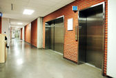 Steel door elevators in deserted hallway — Stock Photo