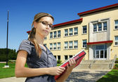 Student in front of school entrance — Stock Photo