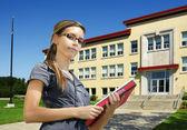 Estudante em frente à entrada da escola — Fotografia Stock