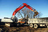 Mechanical digger and truck — Stock Photo