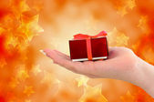 Female hand holding red gift on starry background — Stok fotoğraf